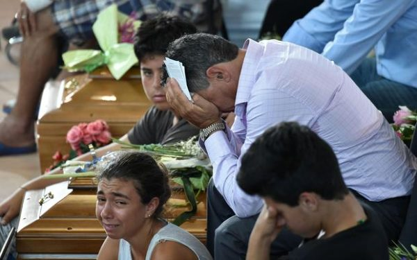 Relatives mourn next to a coffin during a funeral service for victims of the earthquake, at a gymnasium arranged in a chapel of rest on August 27, 2016, in Ascoli Piceno, three days after a 6.2-magnitude earthquake struck the region killing some 281 people. Italy prepared for an emotional day of mourning on August 27, 2016 with flags across the country to fly at half mast in honour of the 281 victims of a devastating earthquake. Grieving families began burying their dead on August 26 as rescue workers combing the rubble said they had found no new survivors in the remote mountain villages in central Italy blitzed by August 24's powerful pre-dawn quake. / AFP / ALBERTO PIZZOLI        (Photo credit should read ALBERTO PIZZOLI/AFP/Getty Images)