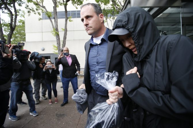 Tiffany Li, right, leaves with a bodyguard from San Mateo County Jail after posting an unprecedented $35 million bail raised by friends, family and business associates with ties to China on Thursday, April 6, 2017, in Redwood City, Calif. (AP Photo/Tony Avelar)
