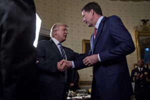 "WASHINGTON, DC - JANUARY 22: U.S. President Donald Trump (C) shakes hands with James Comey, director of the Federal Bureau of Investigation (FBI), during an Inaugural Law Enforcement Officers and First Responders Reception in the Blue Room of the White House on January 22, 2017 in Washington, DC. Trump today mocked protesters who gathered for large demonstrations across the U.S. and the world on Saturday to signal discontent with his leadership, but later offered a more conciliatory tone, saying he recognized such marches as a ""hallmark of our democracy."" (Andrew Harrer/Getty Images)"