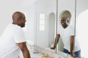 Los Angeles, California, USA --- Man looking in bathroom mirror, smiling --- Image by © Blue Images/Corbis