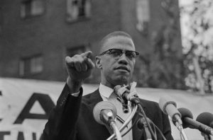 Original Caption: Black Muslim leader Malcolm X, draws various reactions from audience in Harlem rally 6/29. Meeting, at which Malcolm X restated Muslim theme of complete separation of whites and negroes, outdrew a rally sponsored by a civil rights group 10 to 1. This meeting, of the Mississippi-Alabama Southern Relief Committee, was going on at the same time some six blocks away.