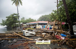 TOPSHOT - People stand next to debris at a restaurant in Le Carbet, on the French Caribbean island of Martinique, after it was hit by Hurricane Maria, on September 19, 2017. Martinique suffered power outages but avoided major damage. / AFP PHOTO / Lionel CHAMOISEAU (Photo credit should read LIONEL CHAMOISEAU/AFP/Getty Images)